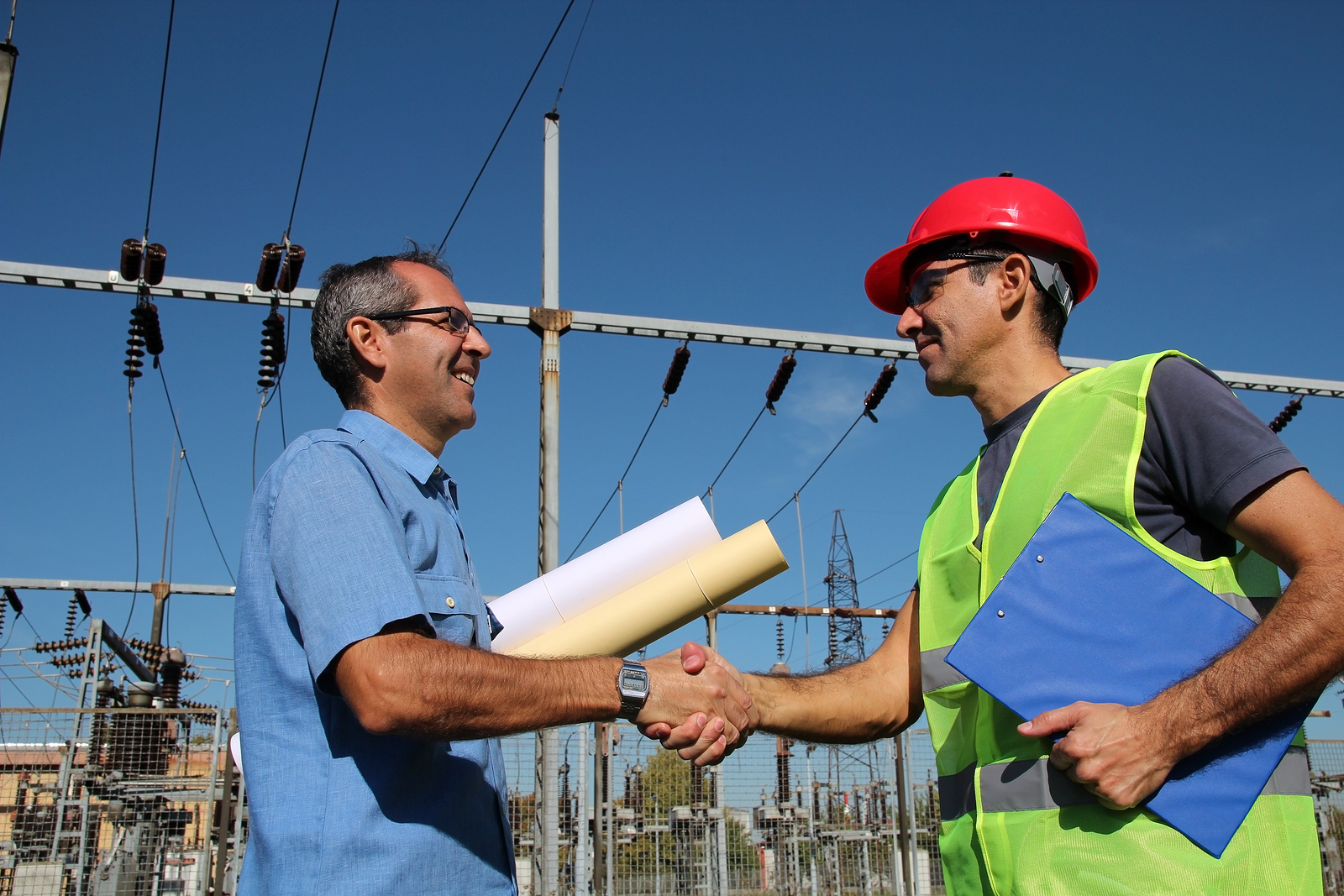 Smiling workers with blueprints and clipboard in meeting at electrical substation. Selective focus.